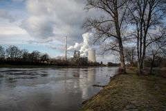 The factory smokes into the air on the shore of a beautiful river stock images