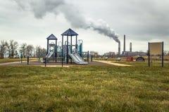 Factory Smokestack Behind Playground Stock Photo