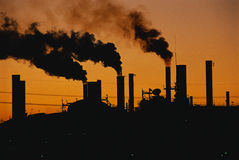 Factory with smokestacks at sunset. This is a Ford factory at sunset. These are smokestacks contributing to the pollution in the air stock photo