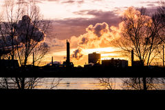 Factory with smokestacks at sunset. With trees and river in the foreground stock photo