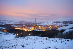 Factory in the snow covered landscape at dusk Royalty Free Stock Image
