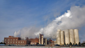 Factory with steam stacks in a cold morning. Steam coming out of a factory royalty free stock photography