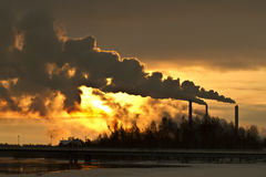 Factory sunset. Sun setting behind factories in winter landscape in Oulu, northern Finland stock images