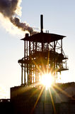 Factory in the sunset. Smoking chimney of an industrial building in the sunset royalty free stock photography