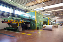 Factory to produce corrugated cardboard. Paper are delivered to corrugators, wrapped around large reels and are processed into sheets of corrugated Royalty Free Stock Photography