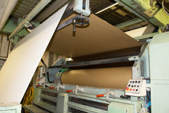 Factory to produce corrugated cardboard. Paper are delivered to corrugators, wrapped around large reels and are processed into sheets of corrugated Stock Image