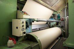 Factory to produce corrugated cardboard. Paper are delivered to corrugators, wrapped around large reels and are processed into sheets of corrugated Stock Photography