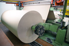 Factory to produce corrugated cardboard. Paper are delivered to corrugators, wrapped around large reels and are processed into sheets of corrugated Stock Images