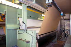 Factory to produce corrugated cardboard. Paper are delivered to corrugators, wrapped around large reels and are processed into sheets of corrugated Royalty Free Stock Photos