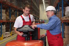 Factory Training. A senior worker teaching his junior the operation of a fork lift vehicle in a factory royalty free stock photo