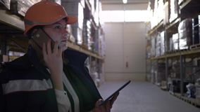 Factory warehouse, female inspector in orange helmet talking on cellular phone and using tablet computer stock video footage