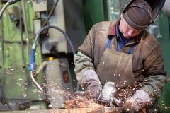 Factory welder worker grinding steel sheet Stock Photo