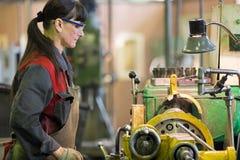 Factory woman turner working at workshop lathe machine. Metalwork industry. Factory woman turner working at workshop lathe machine royalty free stock photo