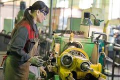 Factory woman turner working on workshop lathe machine. Metalwork industry. Factory woman turner working on workshop lathe machine stock photography