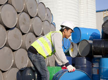 Factory worker. Asian man worker rolling barrel at the factory or warehouse royalty free stock image
