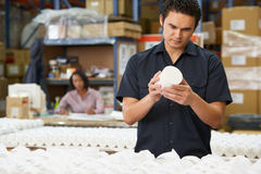 Factory Worker Checking Goods On Production Line Royalty Free Stock Image