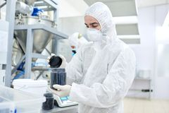 Factory worker closing plastic container with product. Production worker in protective clothing closing black jar with sports nutrition stock images