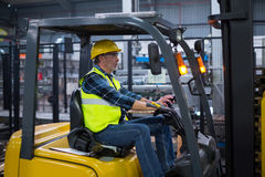 Factory worker driving forklift. In drinks production factory Royalty Free Stock Image