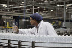Factory worker examining bottled water Royalty Free Stock Image