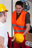 Factory worker giving his collaborator hardhat Stock Photography