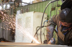 Factory worker grinding steel sheet with flying sparks Stock Photo