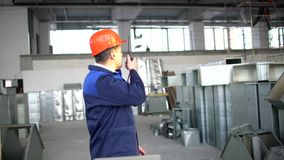 Factory worker in a hard hat is using a laptop computer with an engineering software. Air ducts for conditioning and. Factory worker in a hard hat is using a stock video footage