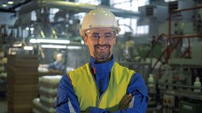 Factory worker in a hardhat is smiling at the camera stock video footage