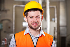 Factory worker in hardhat. Young happy factory worker in yellow hardhat and vest Stock Photography