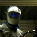 A factory worker. I took this photografy at a factory i used to work in. this man was seaming one iron plate to another, wearing the helmet shielding him against Royalty Free Stock Photography