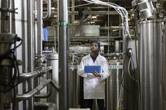 Factory worker inspecting bottling factory Royalty Free Stock Image