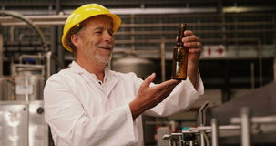 Factory worker inspecting a glass bottle at bottling plant. Smiling factory worker inspecting a glass bottle at bottling plant stock video