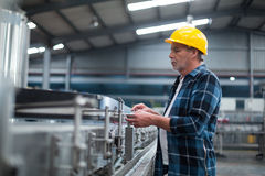 Factory worker monitoring production line. In factory Royalty Free Stock Photography