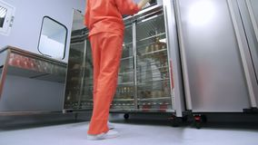 Factory worker in orange protective suit opening refrigerator storage