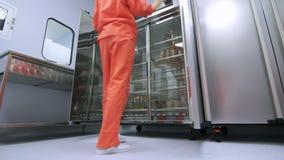 Factory worker in orange protective suit opening refrigerator storage