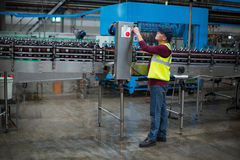 Factory worker operating machine. At drinks production factory Royalty Free Stock Images
