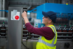 Factory worker operating machine. At drinks production factory Stock Photo