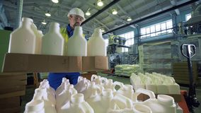 Factory worker puts boxes with bottles in a facility, wrapping process. stock video