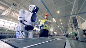 Factory worker is regulating robot`s settings by remote control during working process