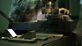Factory worker sets metal piece in vise of a milling machine. Male worker in a plaid shirt and wear protective gloves when using tool loosens grip mount, that stock video