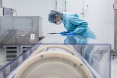 Factory worker stand near machine with tablet, bended. Caucasian factory worker in blue lab suit, with tablet in hands, bend on manufacture machine Stock Image