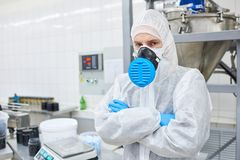 Factory worker standing in protective clothing. Sports nutrition production worker standing in protective clothing with arms crossed and looking at camera royalty free stock photos