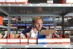 Factory Worker In Store Room Checking Stock. Male Factory Worker In Store Room Checking Stock Royalty Free Stock Photos