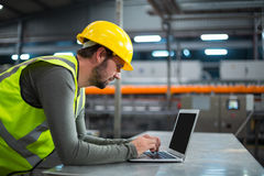 Factory worker using laptop. At drinks production factory Royalty Free Stock Photos