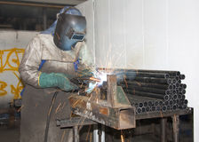 Factory Worker Welding. A Factory Worker Welding tubes / pipes on a production line Stock Photos