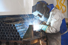 Factory Worker Welding. A Factory Worker wearing protective gear, Welding in a production line Royalty Free Stock Image