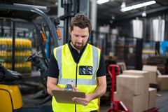Factory worker writing on clipboard in factory. Attentive factory worker writing on clipboard in factory Royalty Free Stock Images