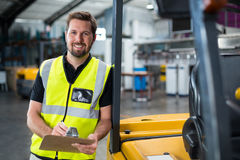 Factory worker writing on clipboard in factory Royalty Free Stock Images