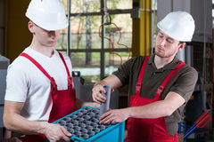 Factory workers and the box of hydraulic pipes Royalty Free Stock Photos