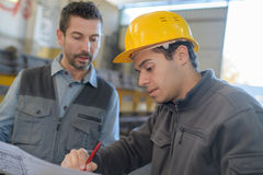 Factory workers checking paper. Factory workers checking a paper royalty free stock photos