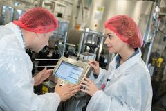 Factory workers in discussion over production line monitor Royalty Free Stock Photo